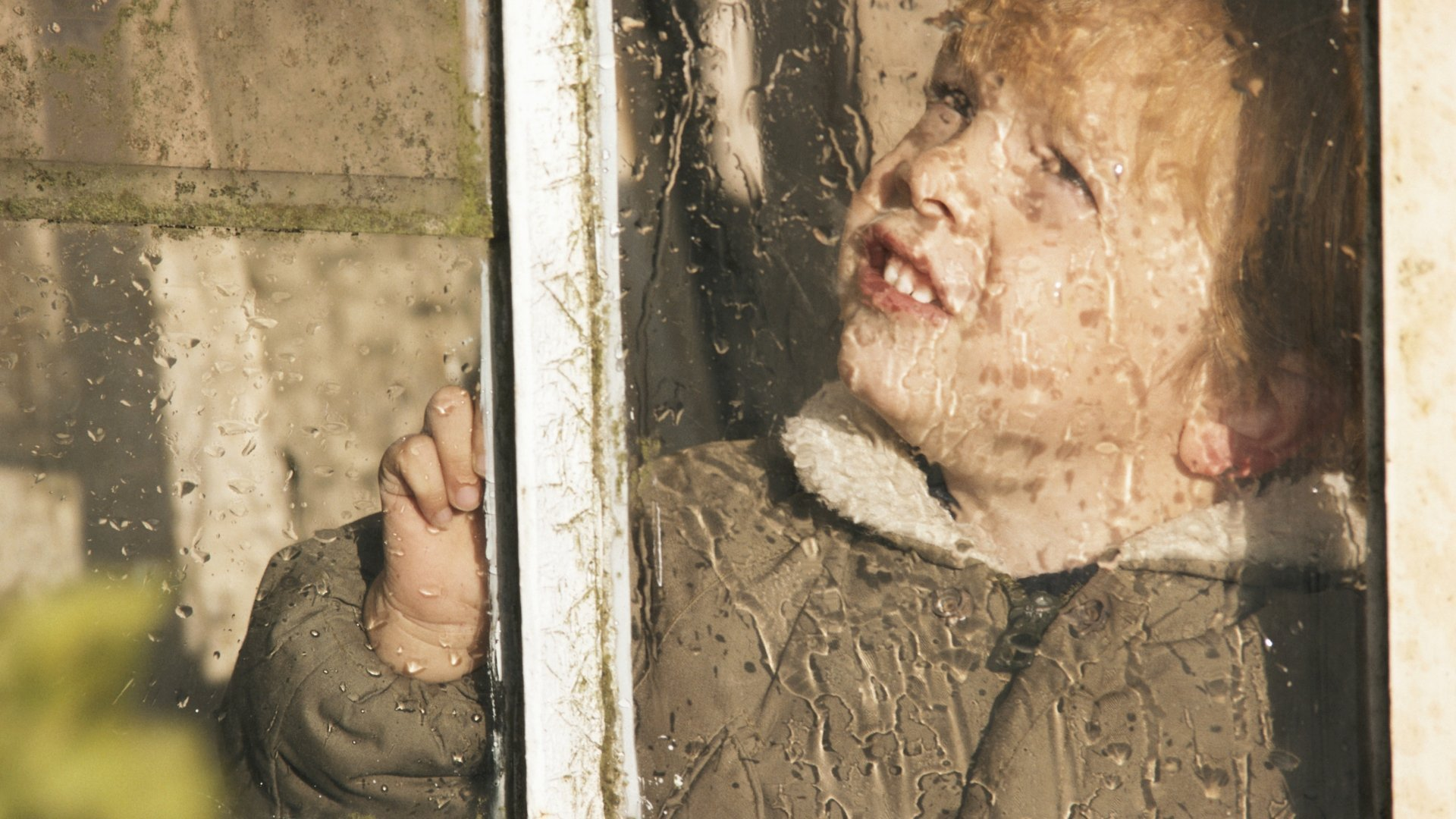 Boy Looking Out Window on Rainy Day