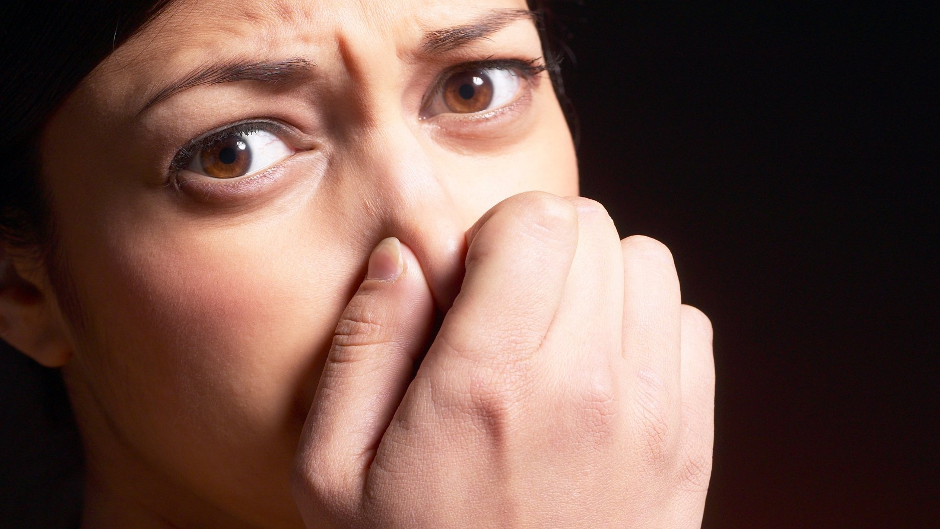 Women Holding Nose Because of Musty Smell